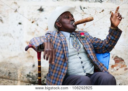 HAVANA, CUBA - JULY 17, 2013: Cuban man posing for photos while smoking big cuban cigar in Havana, Cuba.