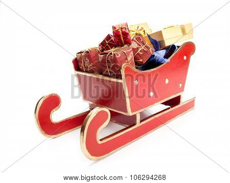 Red sleigh full of christmas presents over white background