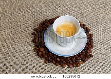 Small Cup Of Espresso In Heap Of Coffee Bean