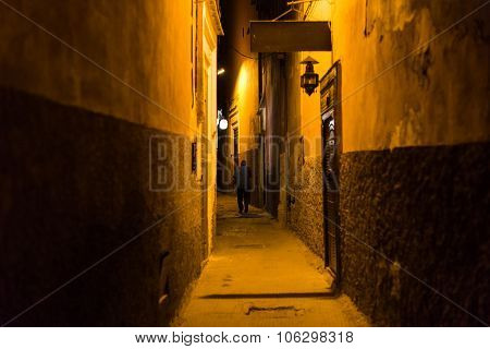 A Guy Walking In A Narrow Side Street At Night