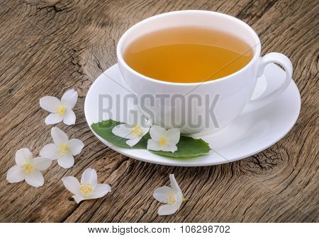 Cup Of Green Tea With Jasmine Flowers On Wooden Background