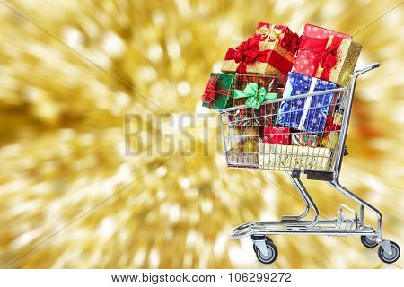 Shopping cart  with gifts over Christmas background.