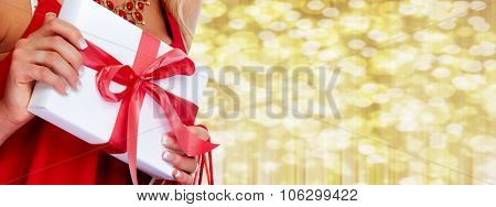 Woman hands with Xmas gift over Christmas background.