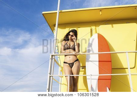Young sexy female standing with surfboard while resting after swimming