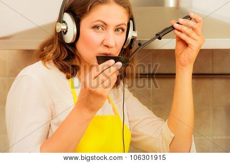 Housewife With Earphones In Kitchen