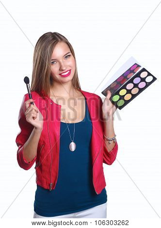Young beautiful woman holds in one hand and a palette with paint and shadows for makeup, second hand