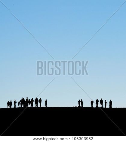 Groups of people silhoetted on horizon