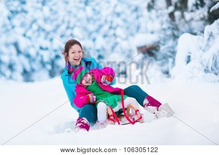 Mother And Child Sledding In A Snowy Park