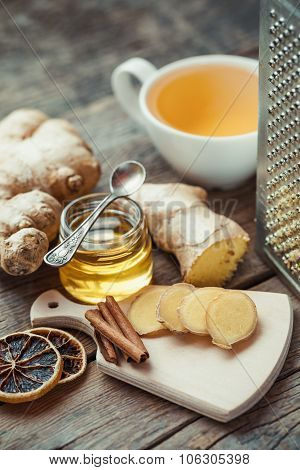 Ginger On Cutting Board, Jar Of Honey, Tea Cup And Grater On Kitchen Table.