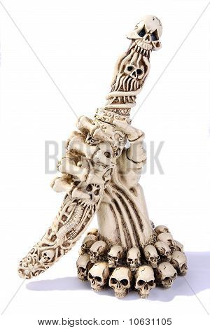Ivory skeleton hand with a paper knife isolated on white background