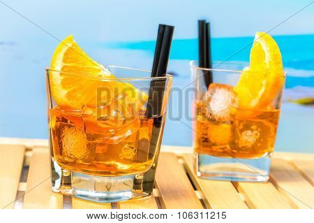 Two Glasses Of Spritz Aperitif Aperol Cocktail With Orange Slices And Ice Cubes On Blur Beach Backgr