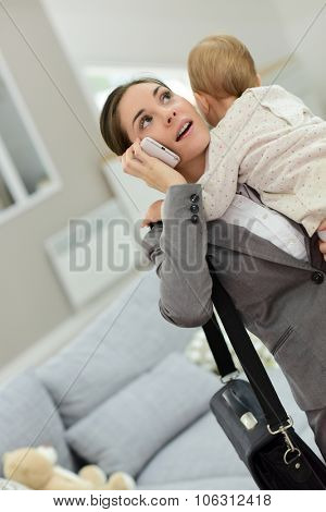 Busy businesswoman talking on phone and holding baby in arms