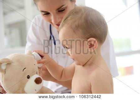 Baby in doctor's office playing with stethoscope and teddy bear