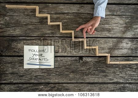 Male Hand Walking His Fingers Up Wooden Steps With A Follow Your Dreams Message