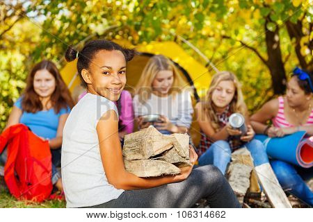 Cute African girl holding kindling wood sitting
