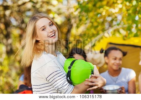 Laughing girl holds sleeping bag sitting at camp