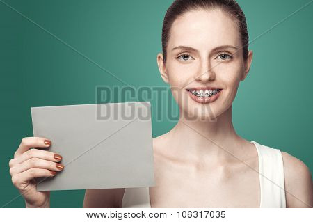 Beautiful Girl With Braces And Gray Card In Hands