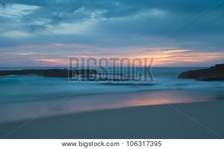 Long exposure of rocks in waves at sunset