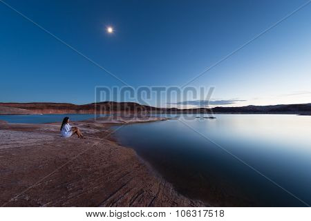 Single Woman Sitting By The Lake Under The Moon Light