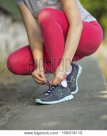 Sports girl ties the laces on sneakers, outdoors, close-up.