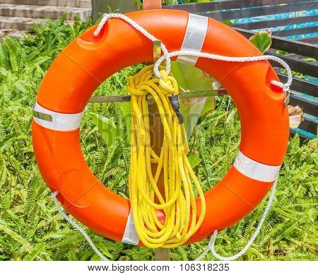 The Orange Life Buoy With Rope Knot Is Hanging Nearby The Hotel Swimming Pool, For Safety And Rescue