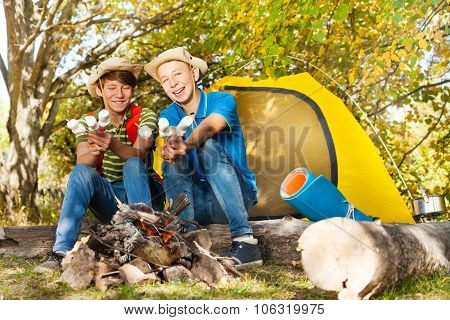 Two boys with hats hold marshmallow sticks