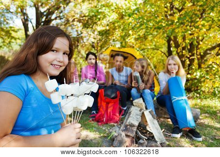 Smiling girl holding sticks with marshmallow