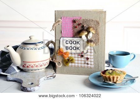 Decorated cookbook with teapot and tasty cake on white background