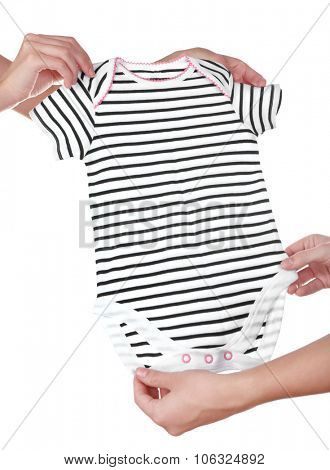 Concept of childish goods sale -one woman hand gives baby's striped overall to another, isolated on white background