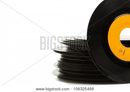 Stack of old single vinyl records, one upright in front with copy space on white background