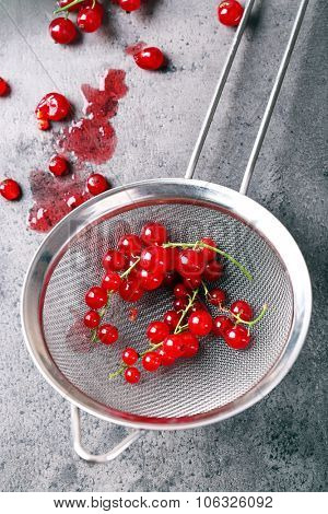 Fresh red currants in sieve close up