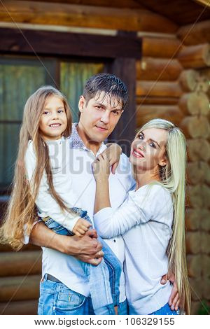 Happy young family near the wooden house