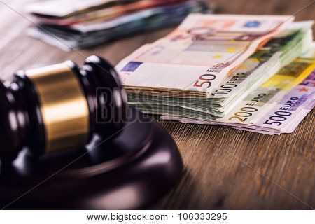 udge's hammer gavel. Justice and euro money. Euro currency. Court gavel and rolled Euro banknotes.