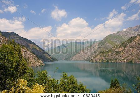 Colorful lake with mountains, sky and clouds