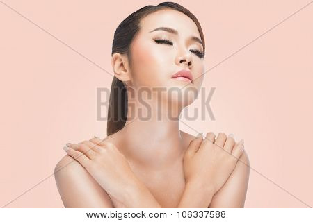 Young asian woman with crossed arms. clean skin resting after skincare