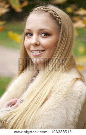 Young beautiful blonde women in a leather sheepskin coat on golden autumn background