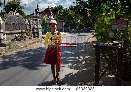 Indonesian Girl Bring Offerings To The Home Temple