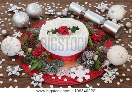 Christmas cake with holly, bauble decorations and winter greenery over oak background.