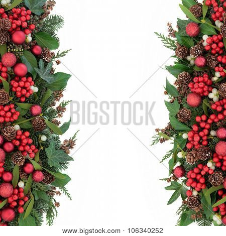 Christmas background border with red bauble decorations, holly, mistletoe, ivy, fir, pine cones and traditional winter greenery over white.