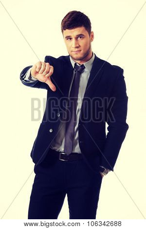 Disappointed young business man with thumb down.
