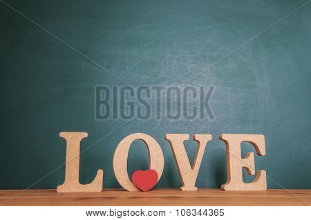 Love message written in wooden blocks on the green background