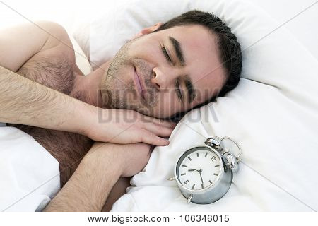Man Sleeping In Bed With Alarm Clock