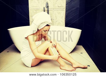 Woman shaving her leg in bathroom.