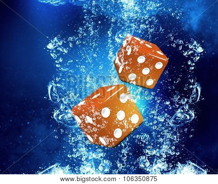Conceptual image with dice cubes in clear blue water