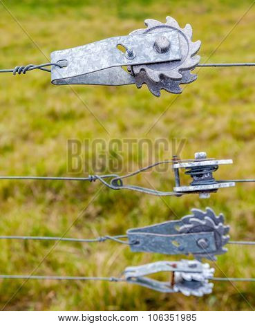 Ratchet Fence Tensioners For Tightening Wire Fences With Blurred Farmland Background.