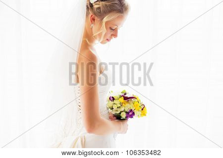 Bride with veil standing by the window