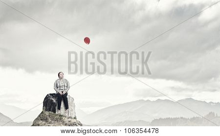 Middle aged stout woman sitting on rock top