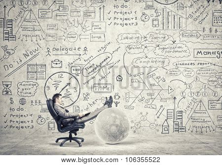 Young businessman sitting in chair and reading book in hands