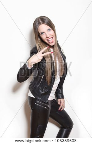 young blonde woman making faces and gestures, wearing black leather jacket and leggings, studio white