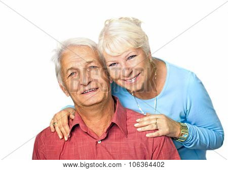 Senior woman standing behind her husband, embracing him
